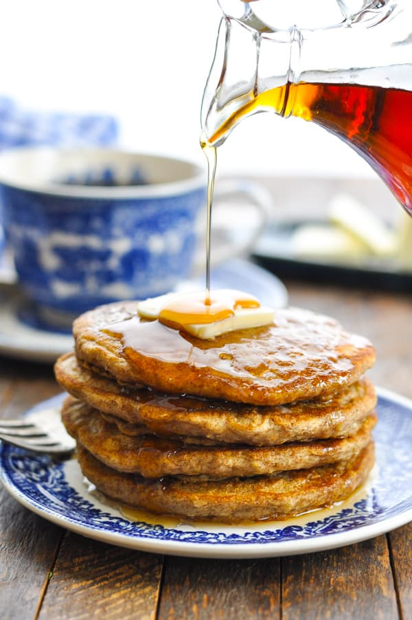Pouring maple syrup on a stack of four oatmeal pancakes