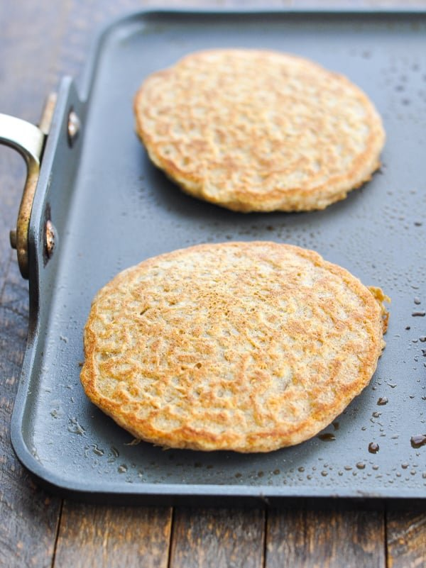 Cooked oatmeal pancakes on a hot griddle