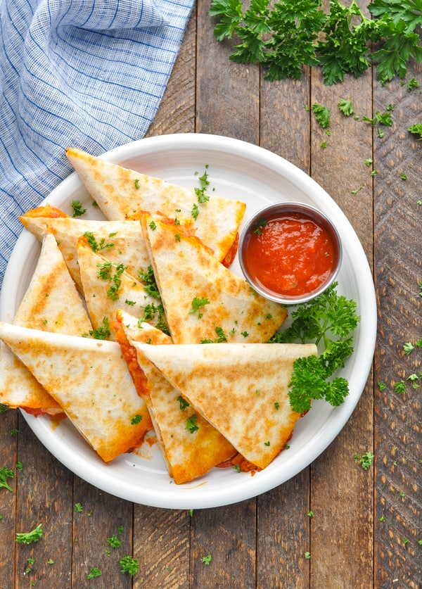 Overhead image of plate of pizza quesadillas garnished with fresh parsley