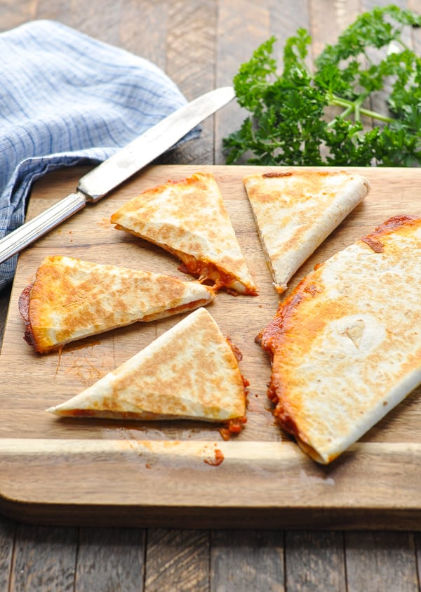 Pizza quesadilla sliced into triangles on a cutting board