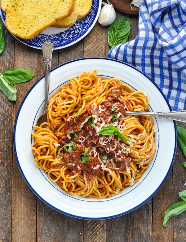 Overhead image of blue and white bowl full of spaghetti meat sauce garnished with fresh basil and parmesan