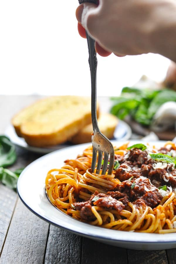 Twisting spaghetti with meat sauce on a fork