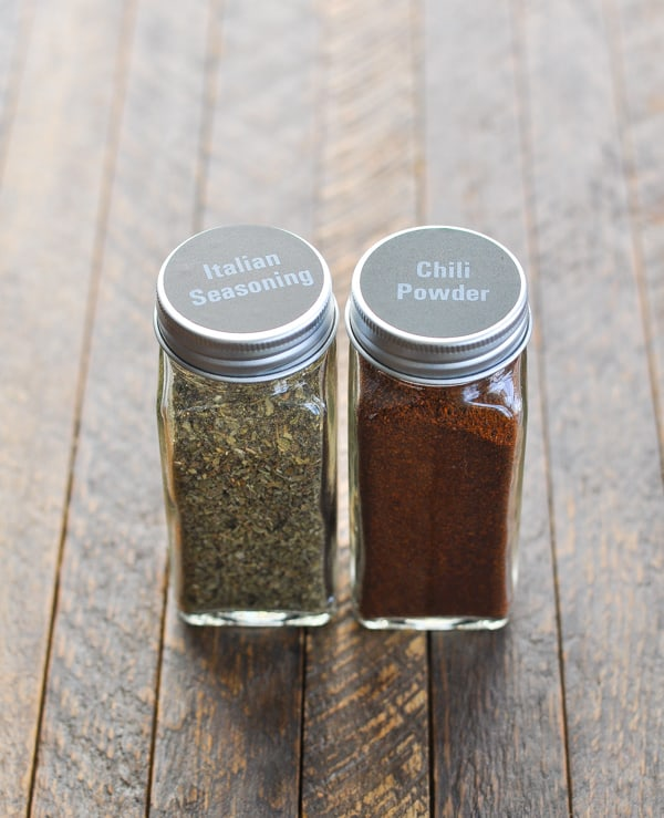 Italian seasoning and chili powder in glass jars