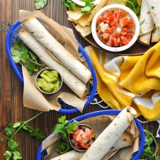 Long overhead shot of baskets of baked taquitos with guacamole and fresh salsa