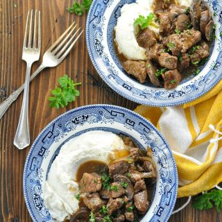 Two bowls of beef tips with mushroom gravy over mashed potatoes