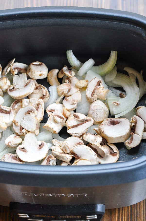 Mushrooms and onions in the bottom of a slow cooker