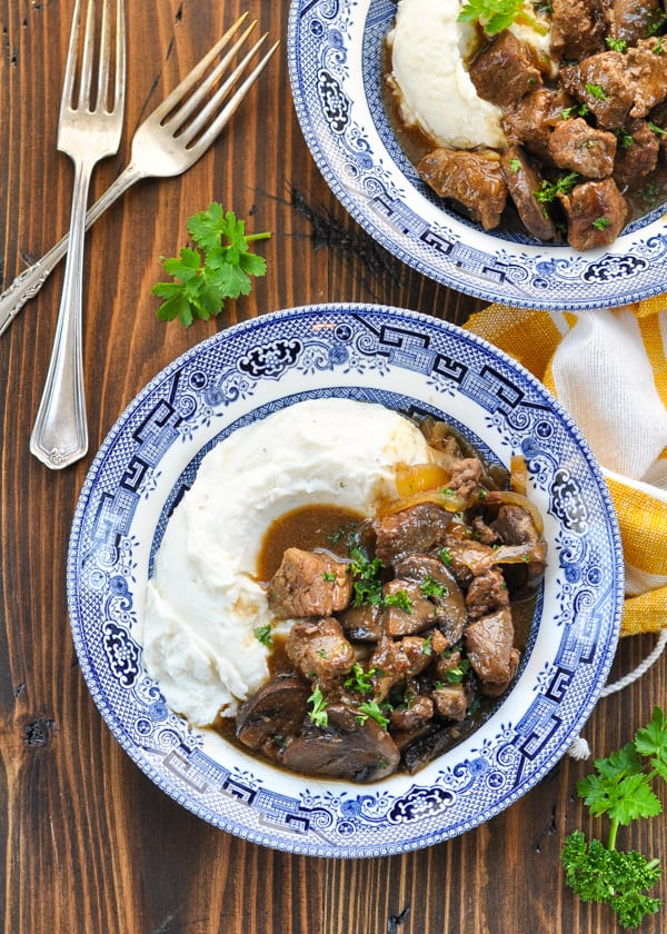 Overhead shot of beef tips with gravy in two bowls with two forks on the table