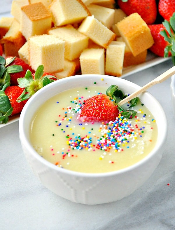 Strawberry on a stick in a bowl of white chocolate fondue