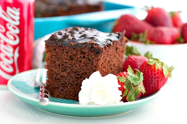 Horizontal image of coca cola chocolate cake on a plate with whipped cream and strawberries