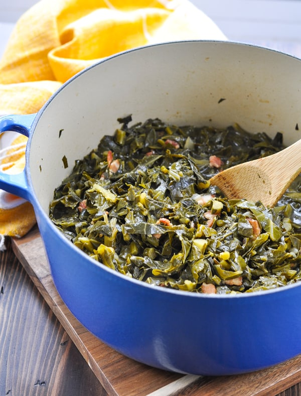 Large blue dutch oven with cooked collard greens inside