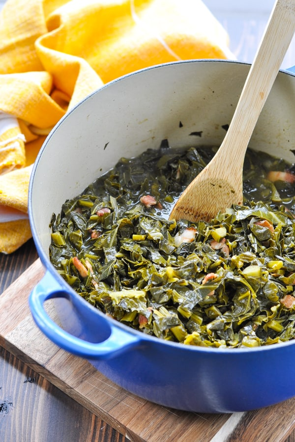 Close shot of collard greens with bacon in a pot