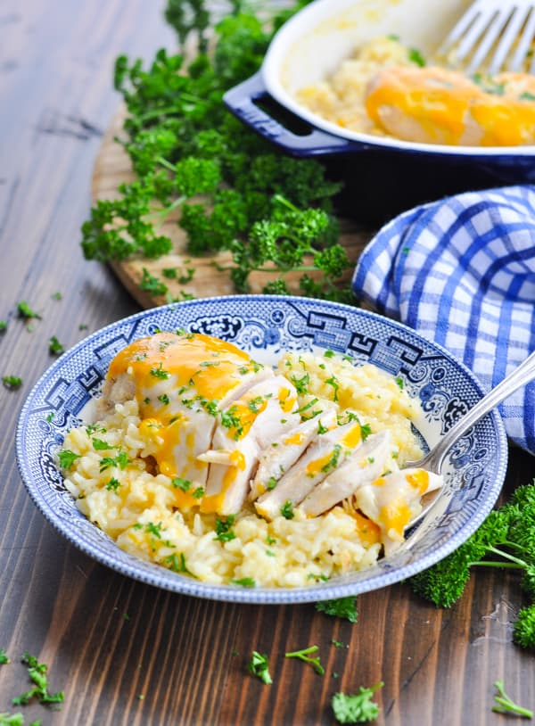 One dish chicken and rice casserole in a blue bowl with baking dish in the background