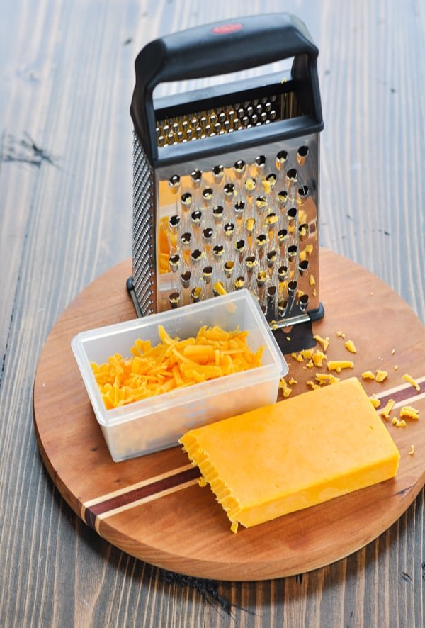 Grated cheddar cheese on a cutting board