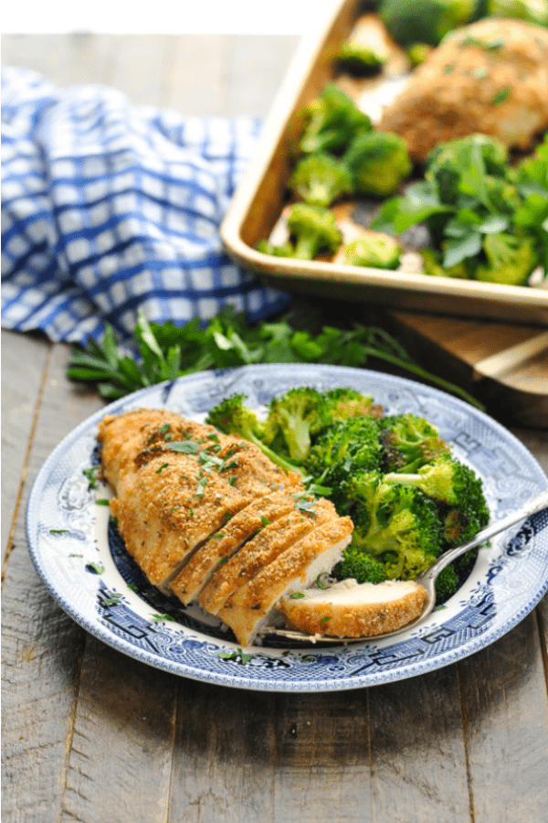 Front view of sliced garlic parmesan chicken with broccoli on a plate