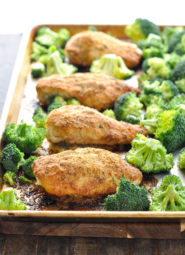 Parmesan crusted chicken breasts on a baking sheet with broccoli florets added at the end