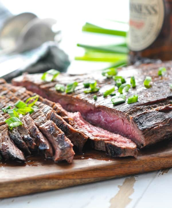 Sliced grilled marinated flank steak on a cutting board