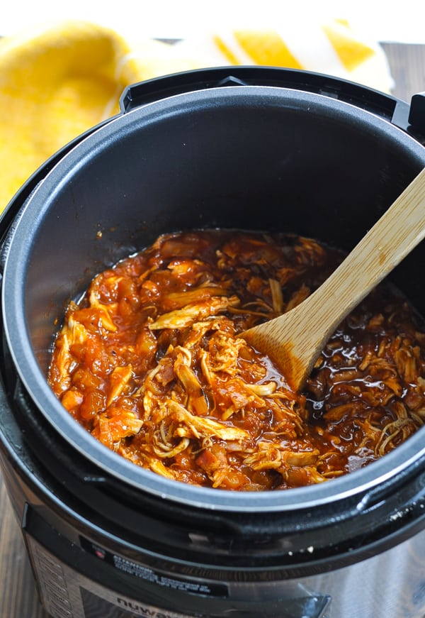 Pineapple and bacon pulled Hawaiian Chicken in an Instant Pot with wooden spoon