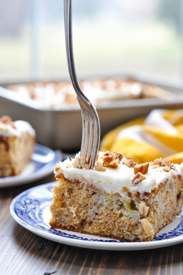 Close up shot of slice of hummingbird cake with a fork in it
