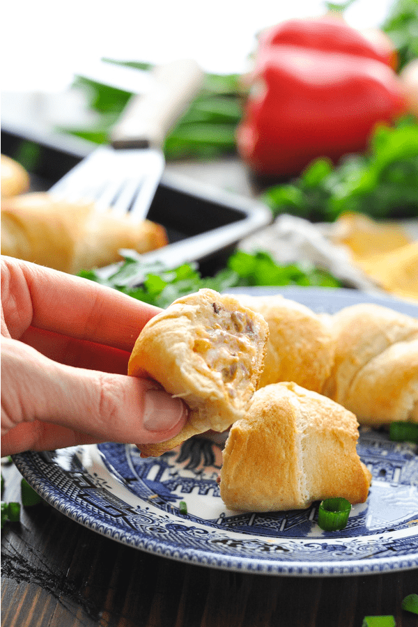 Fingers holding a sliced crescent roll that's stuffed with roast beef and cheese