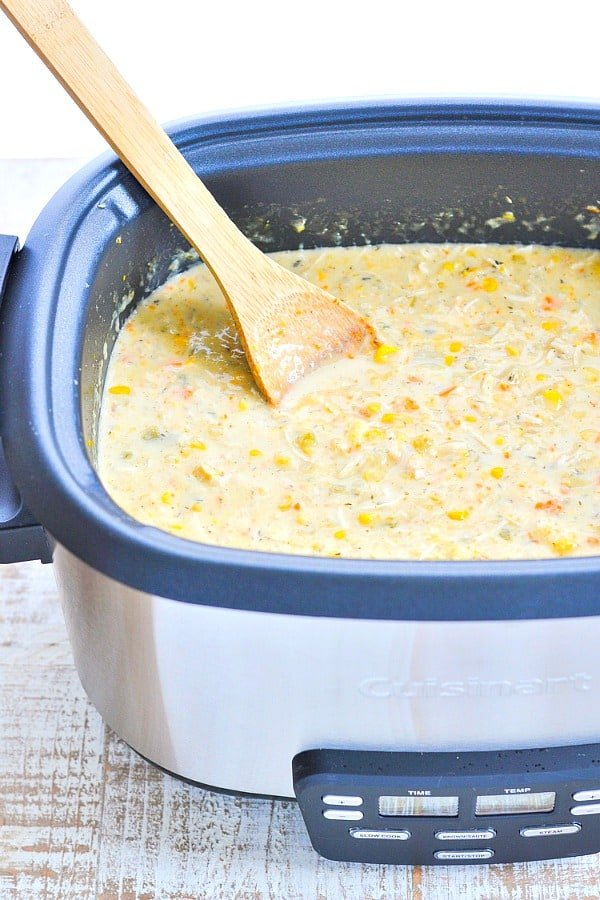 Corn Chowder with a wooden spoon in a slow cooker