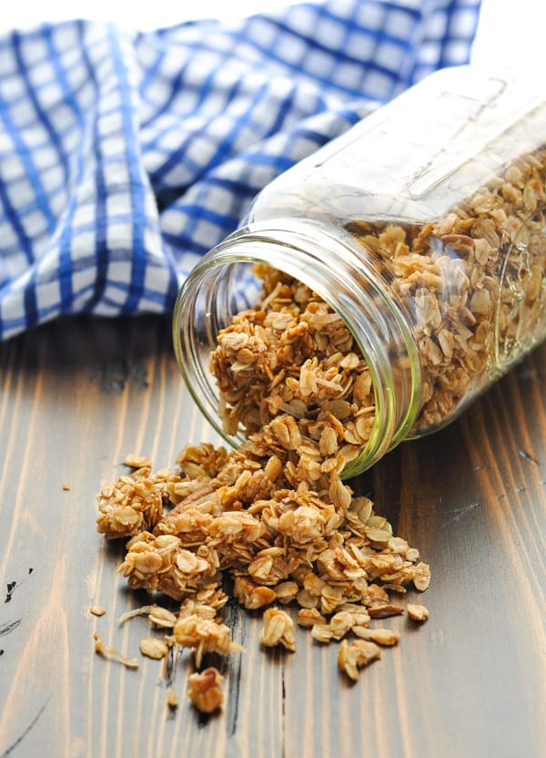 Crunchy vegan cinnamon pecan granola pouring out of glass mason jar