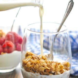 Pouring milk in a glass of crunchy vegan Stovetop Cinnamon Pecan Granola