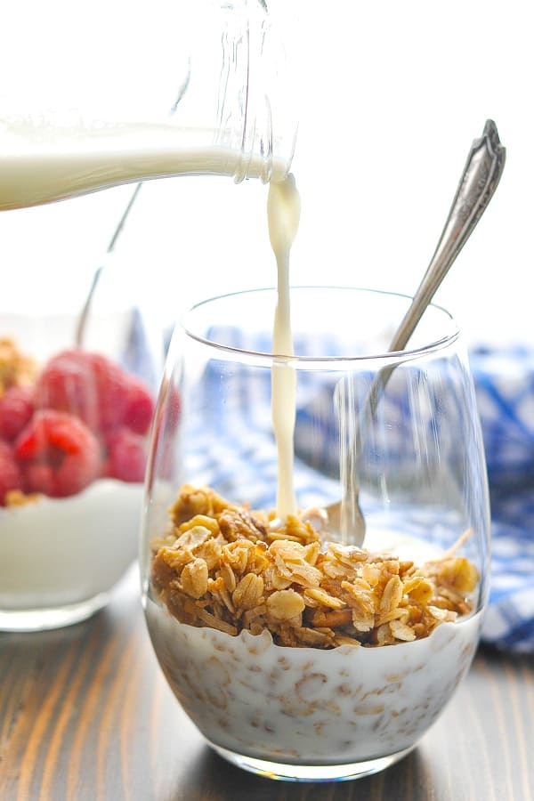 Pouring milk in a glass of crunchy vegan Stovetop Cinnamon Pecan Granola