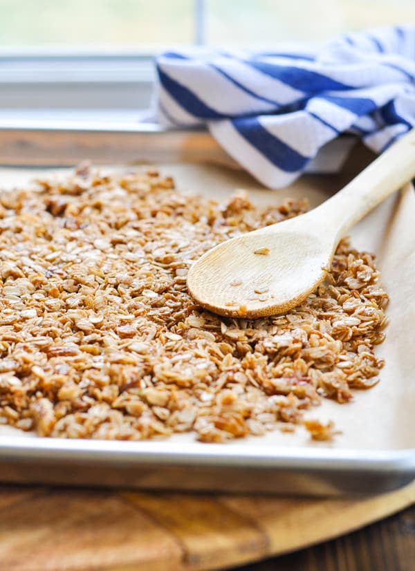 Spreading granola to cool on a baking sheet