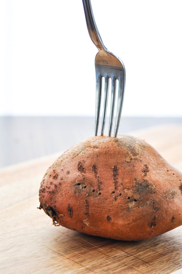 Pricking a sweet potato with a fork