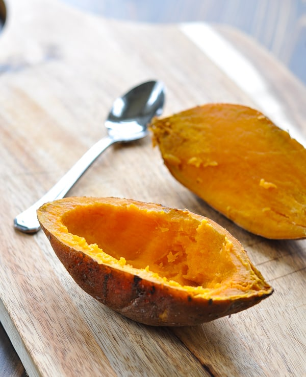 Hollowing out a sweet potato skin on a cutting board