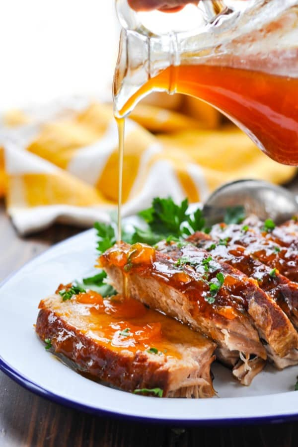 Pouring apricot sauce on Crock Pot Pork Roast