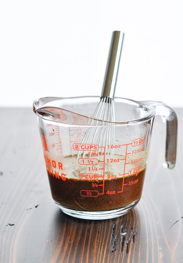 Marinade for a crock pot pork roast in a glass measuring cup with whisk