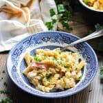 Chicken bacon ranch pasta in a bowl with fresh parsley in the background