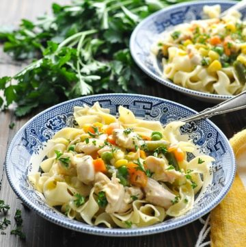 Front view of two bowls of creamy garlic chicken with vegetables and noodles