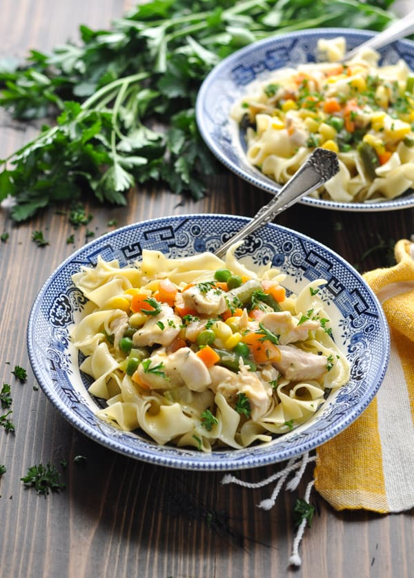 Baked chicken in a garlic cream sauce with vegetables and pasta in a bowl