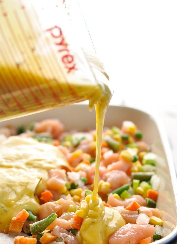 Pouring cream sauce over chicken and vegetables