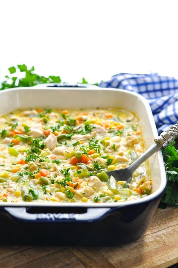 Garlic chicken with vegetables in a creamy sauce in a blue casserole dish