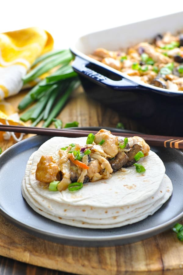 Baked moo shu chicken on top of stack of tortillas with chopsticks
