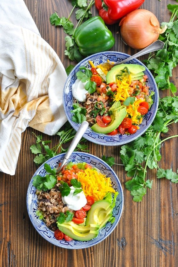 Long overhead shot of two vegetarian burrito bowls surrounded by fresh vegetables and herbs
