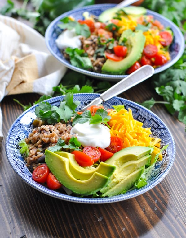Burrito bowls topped with avocado cheese and tomatoes