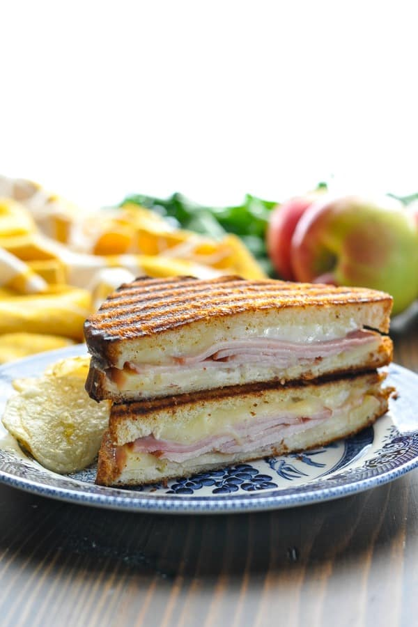 Two halves of a Ham Brie and Apple Panini Sandwich stacked on top of each other on a plate