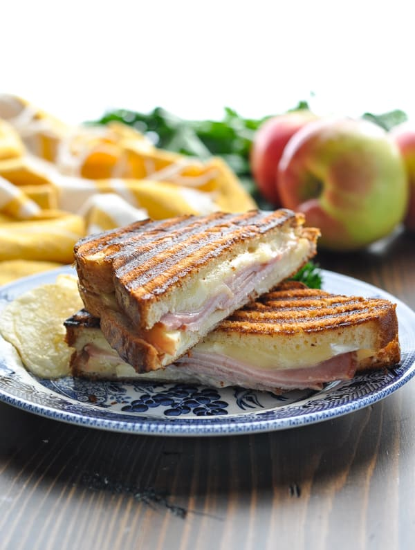 Close shot of ham panini on a plate with apples in background