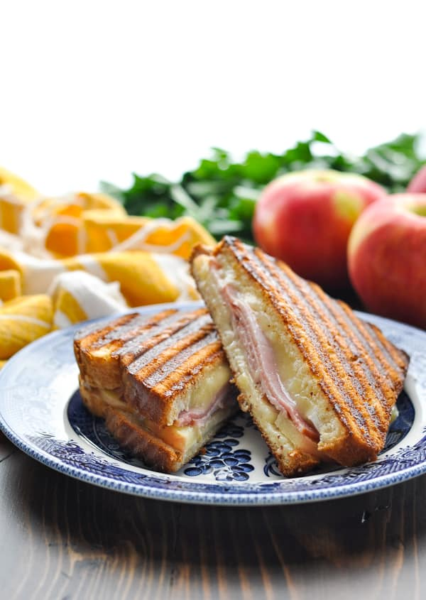 Ham Apple and Brie Cheese Panini Sandwich on a blue and white plate with yellow and white striped towel in background