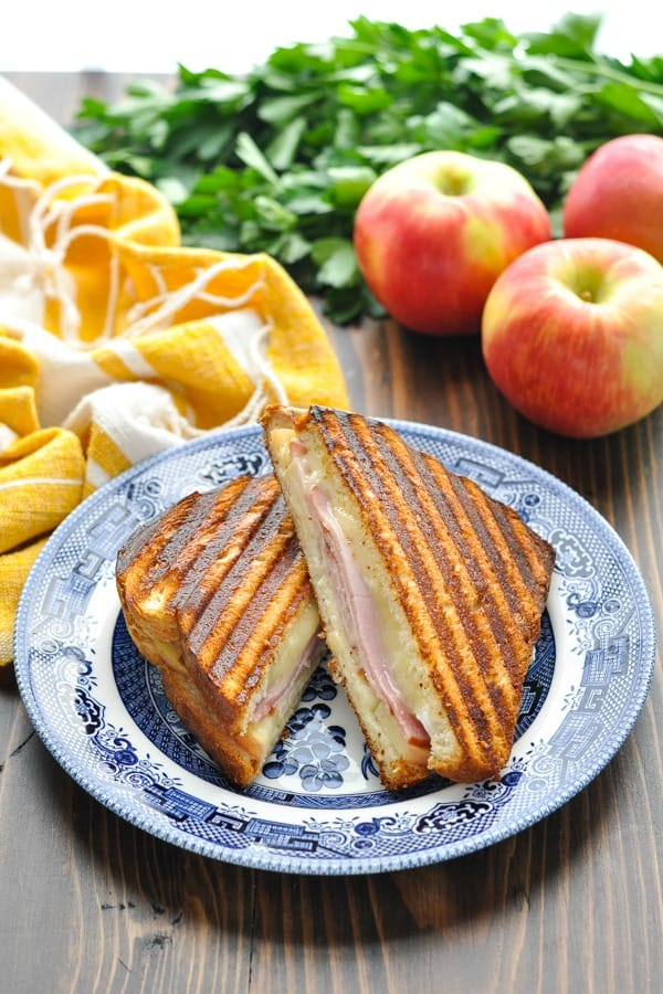 Ham and Cheese Panini Sandwich on a blue and white plate with fresh apples in the background