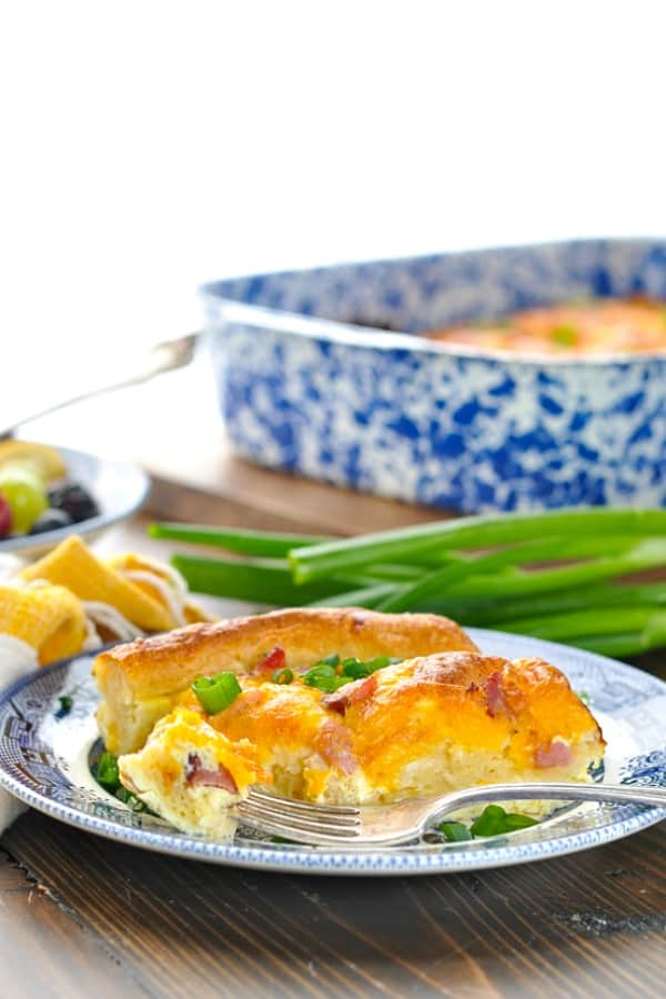 Slice of ham and cheese egg casserole on a plate with green onions in the background