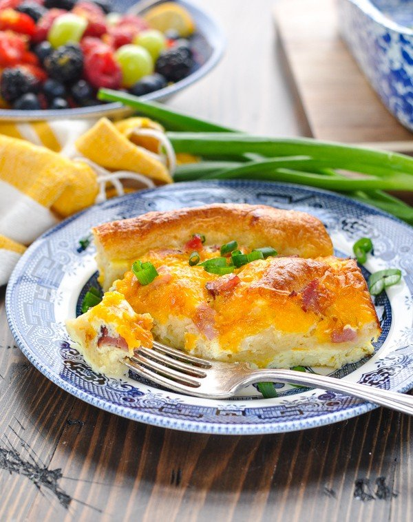 Piece of egg casserole on a plate with a bite on a fork