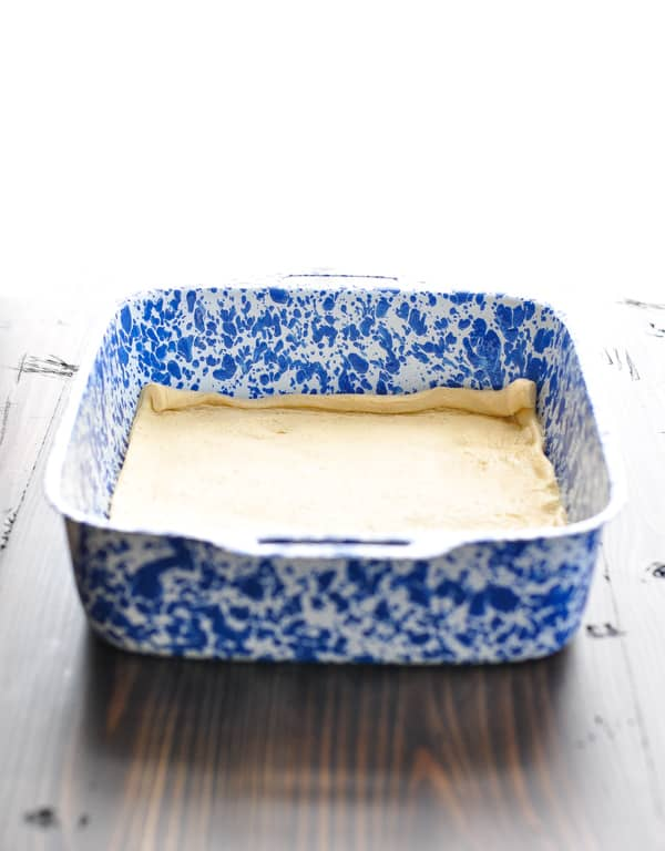 Crescent roll dough sheet unrolled in a blue and white baking dish