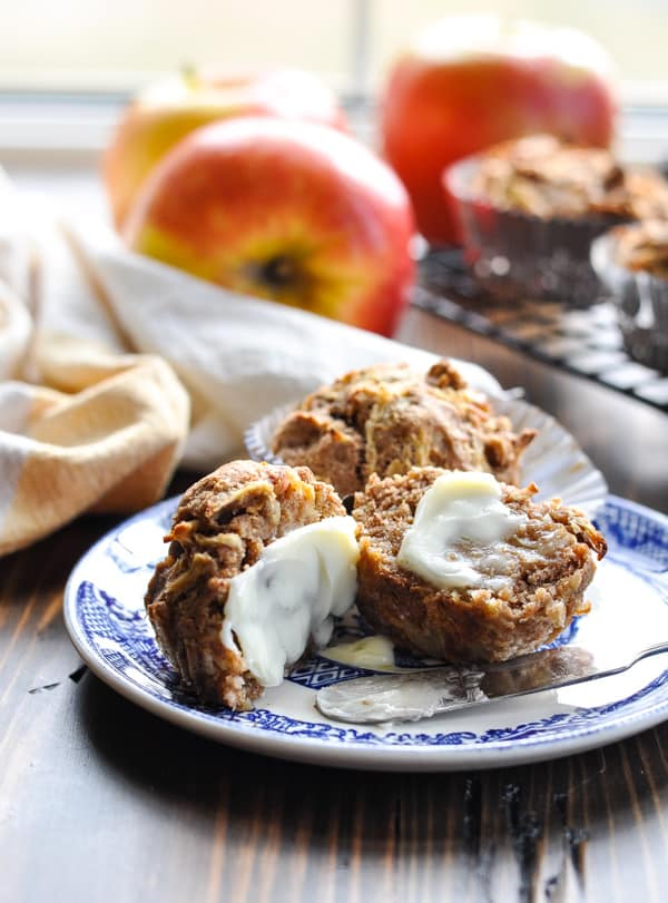 Healthy apple muffins on a blue and white plate with apples in the background