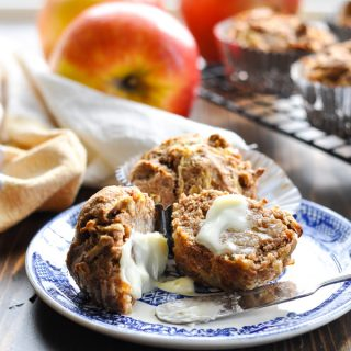 Close up shot of buttered apple muffins on a blue and white plate