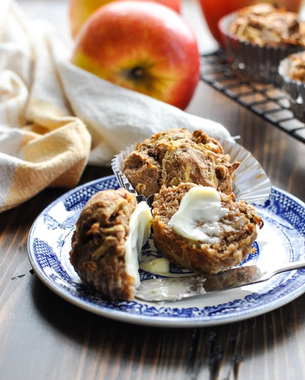 Apple muffins on a plate with butter spread on top